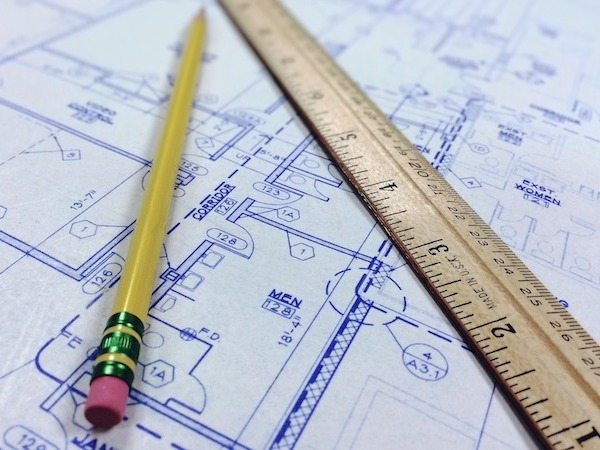 Yellow pencil and wooden ruler on top of blue & white architectural plans