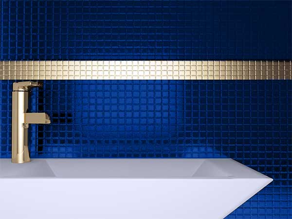 Bright gold fixtures help to set off the deep blue colors of a mermaid trend bathroom
